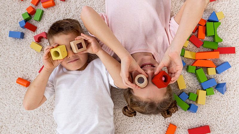 Kids lying on floor palying with wooden blocks